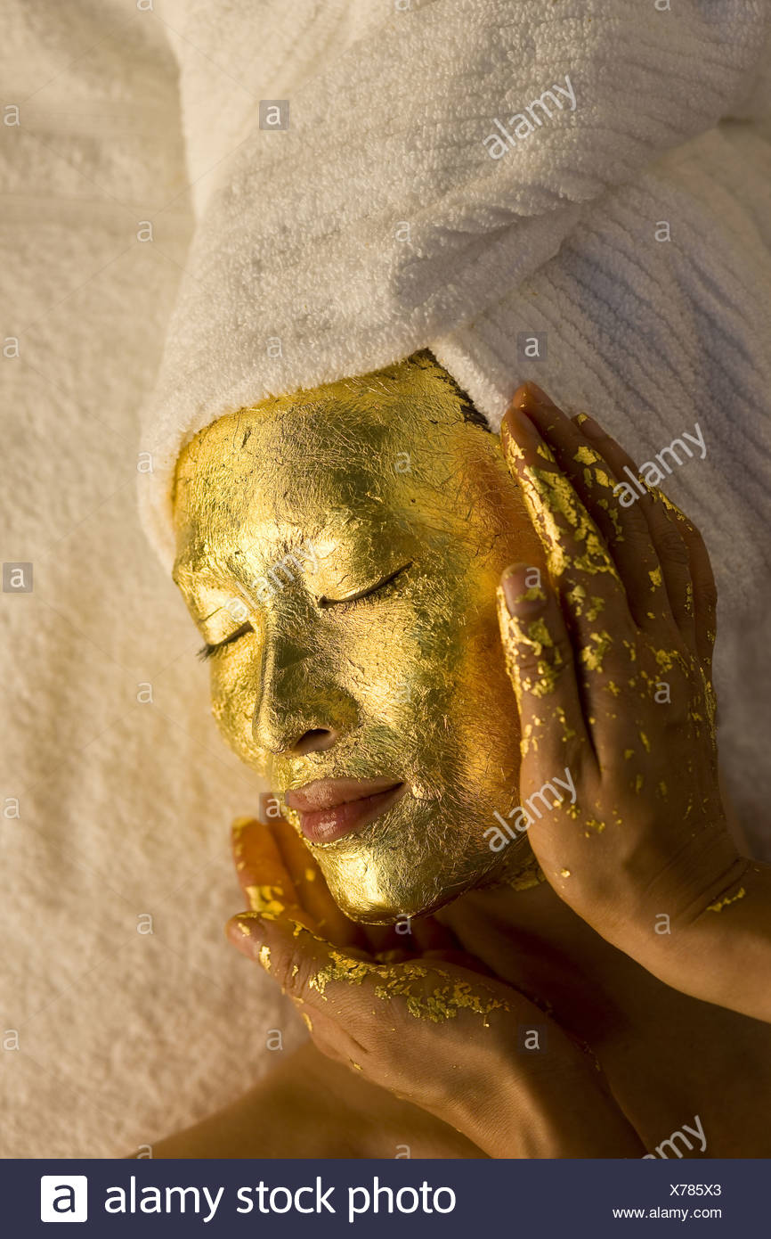 A model receiving a gold facial valued at three hundred dollars. - Stock Image