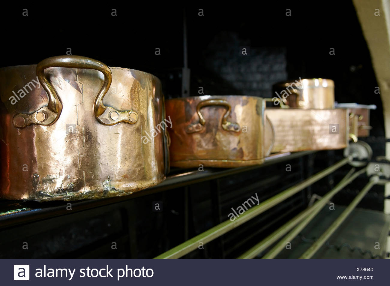 Traditional copper pots and pans in a restaurant kitchen - Stock Image