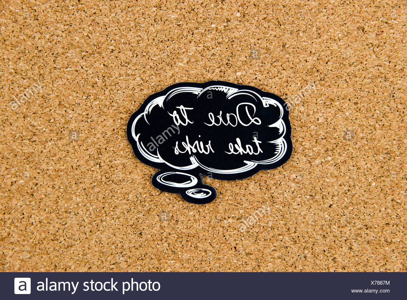 DARE TO TAKE RISKS written on black thinking bubble over cork board background, copy space available - Stock Image