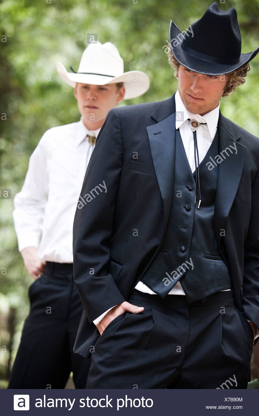 Portrait of two young men in cowboy hats and formal western attire outdoors - Stock Image