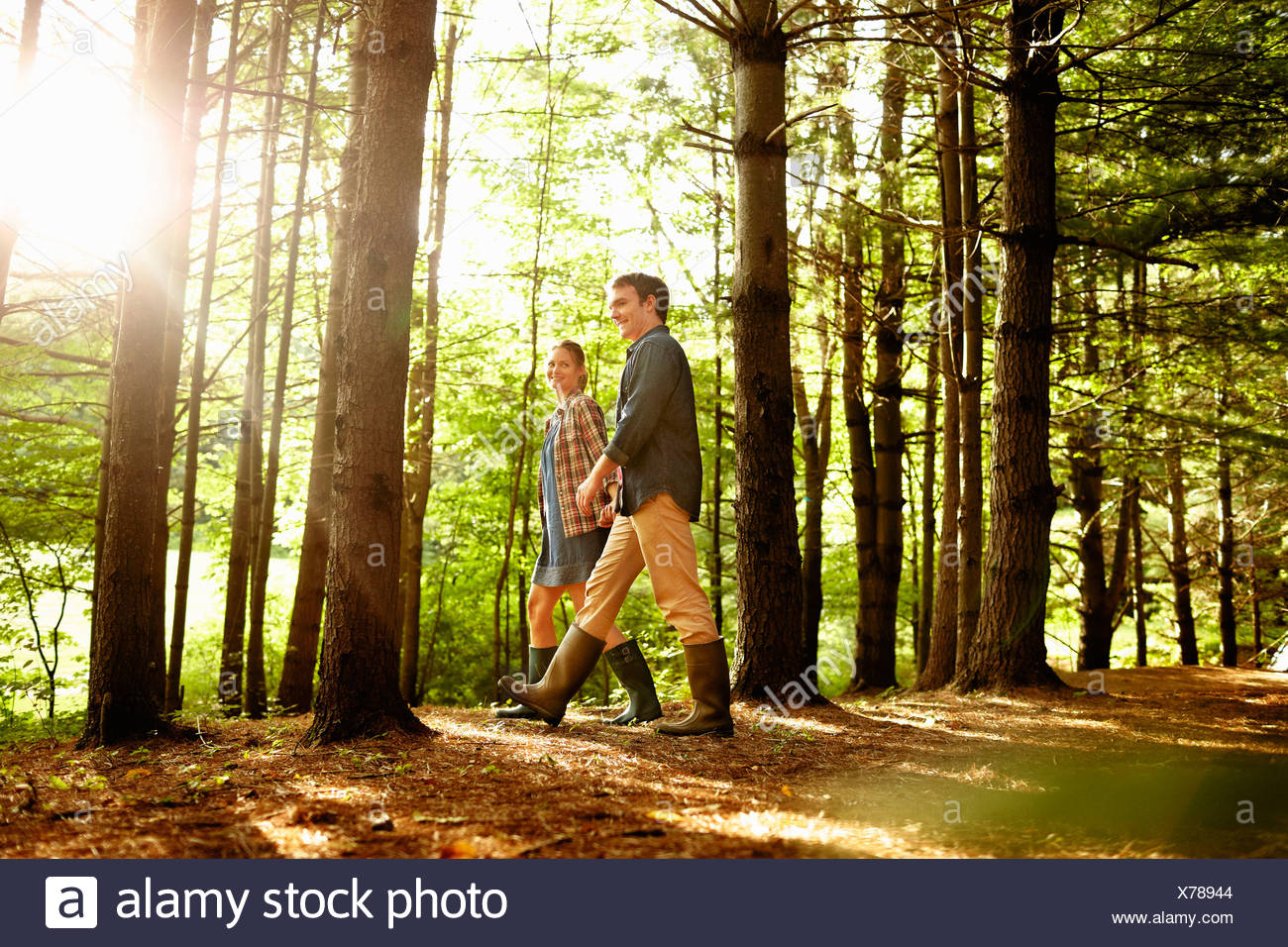 Three people, a family walking in woodland in the late afternoon. - Stock Image