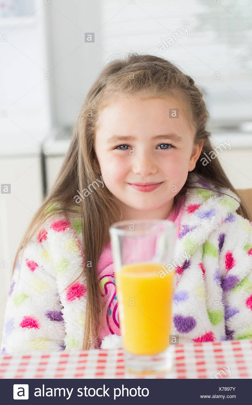 Little girl sitting while smiling with glass of orange juice - Stock Image