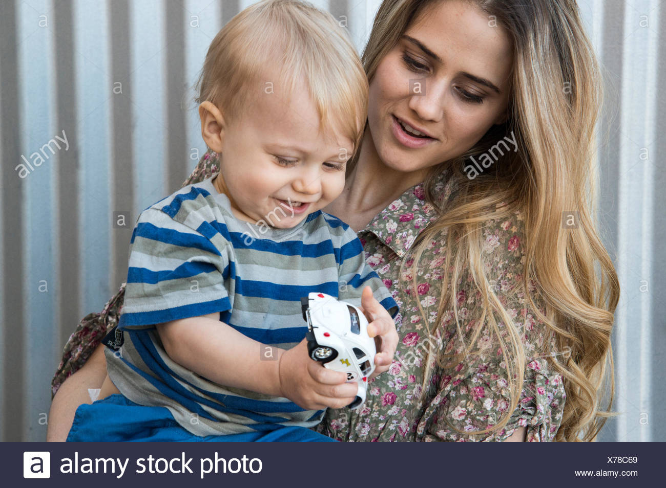 Mother watching her child (12-17 months) play with toy car Stock Photo