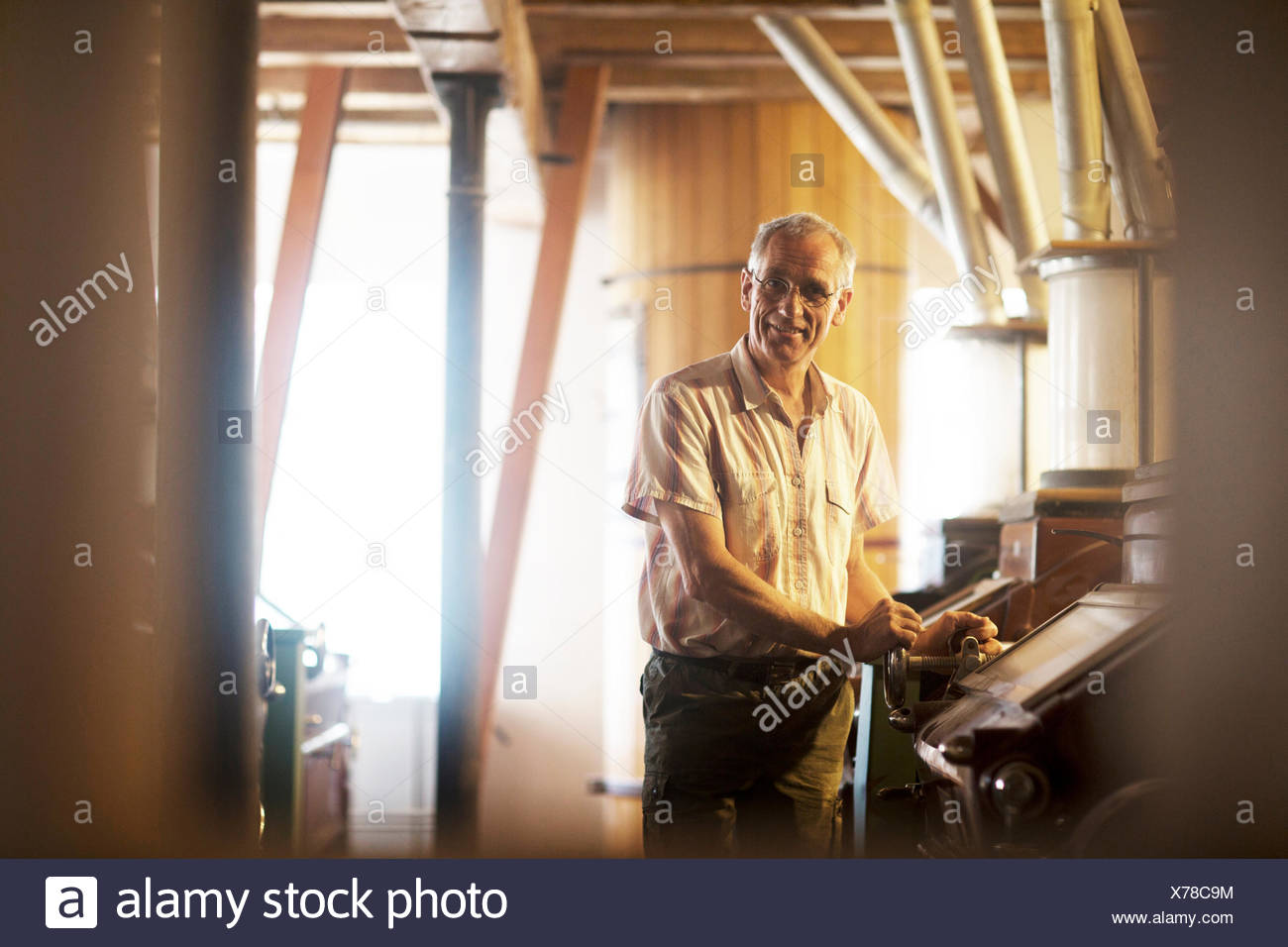 Portrait of male miller operating machine at wheat mill - Stock Image