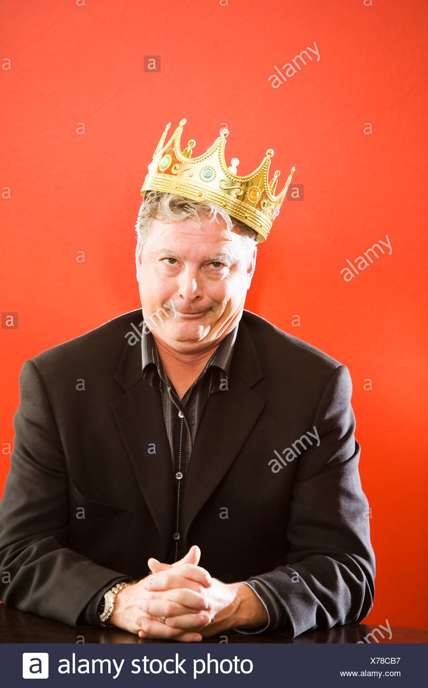 Close up of businessman wearing gold crown - Stock Image