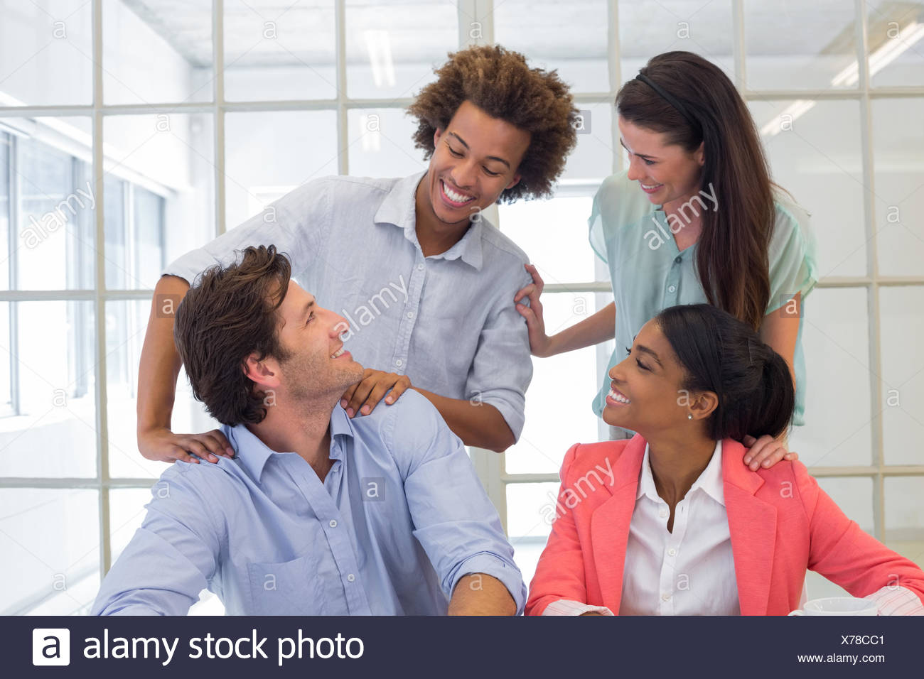 Workers congratulating and praising one another - Stock Image