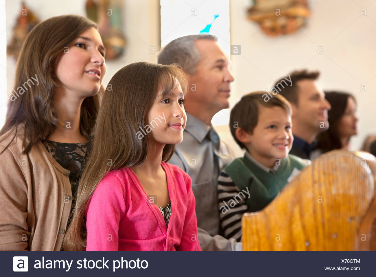 Family sitting together in church - Stock Image