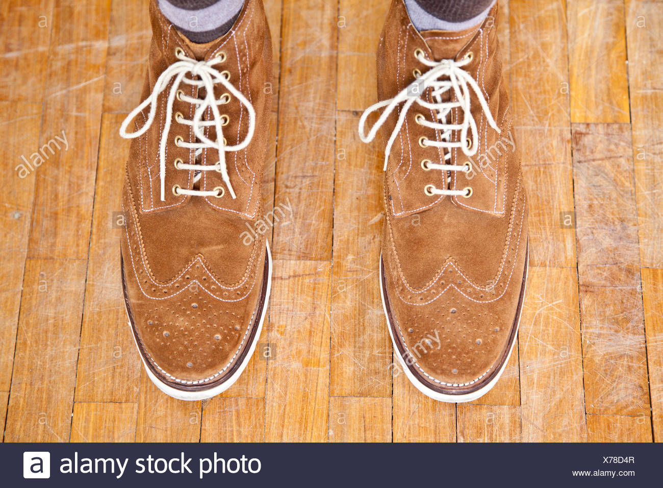 Close up of mans feet wearing suede boots - Stock Image