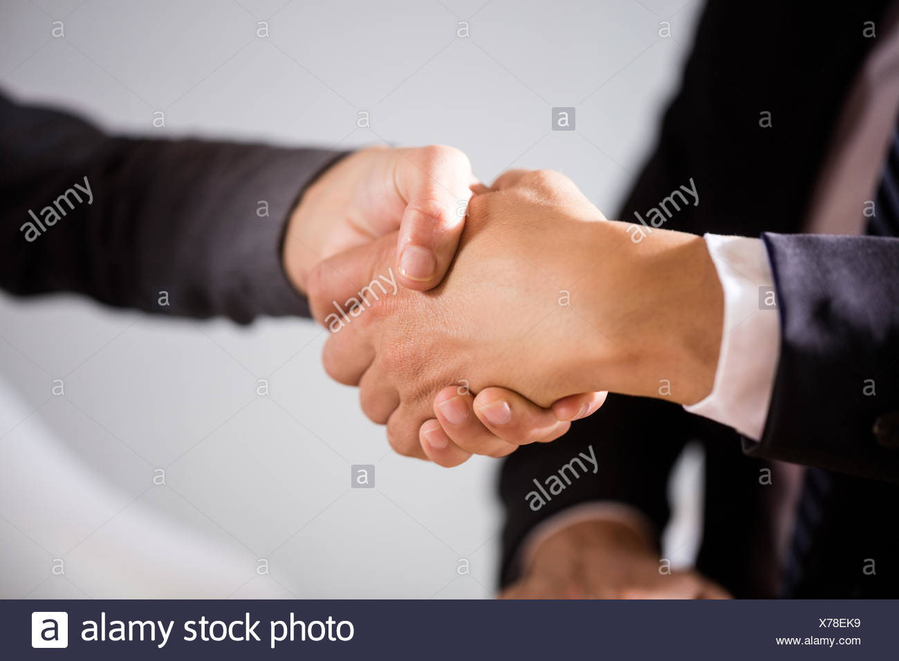 Close up view of business people shaking hands - Stock Image