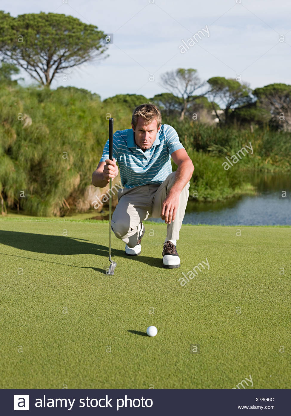 Man playing golf, on putting green - Stock Image