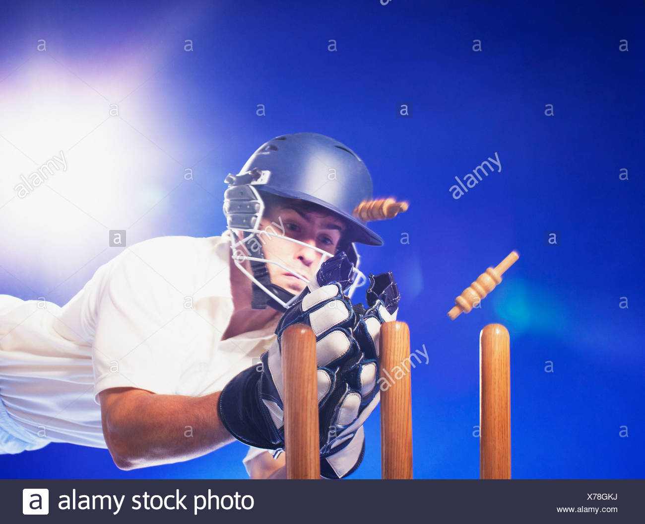Cricket player reaching for bats - Stock Image