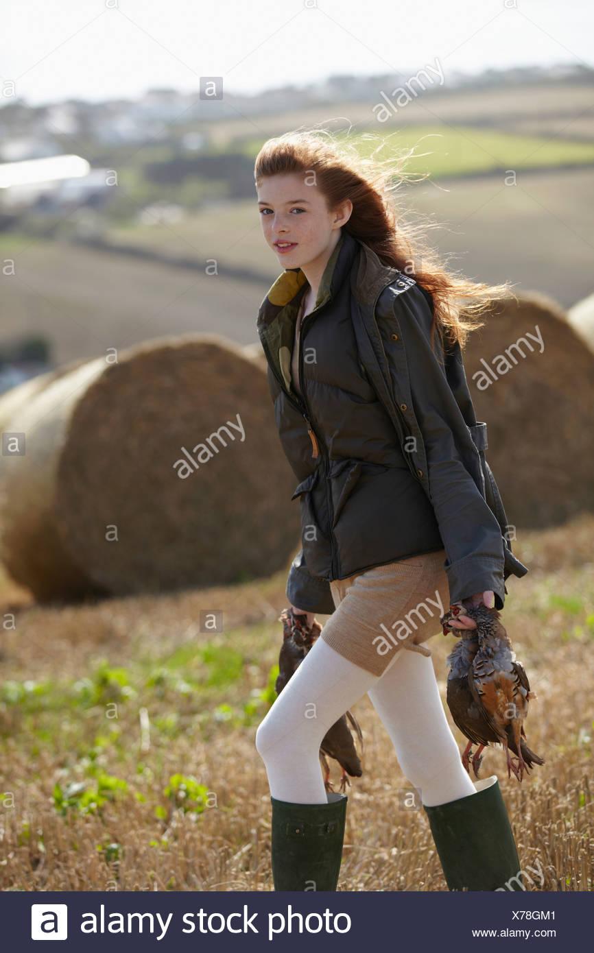 Teenage girl carrying game birds - Stock Image