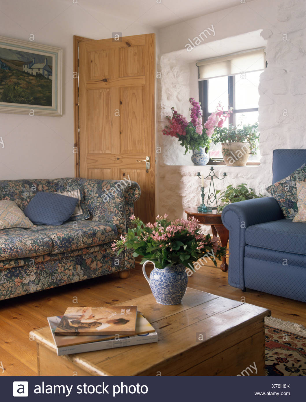 Old pine chest and blue patterned chesterfield sofa with a blue armchair in a nineties cottage