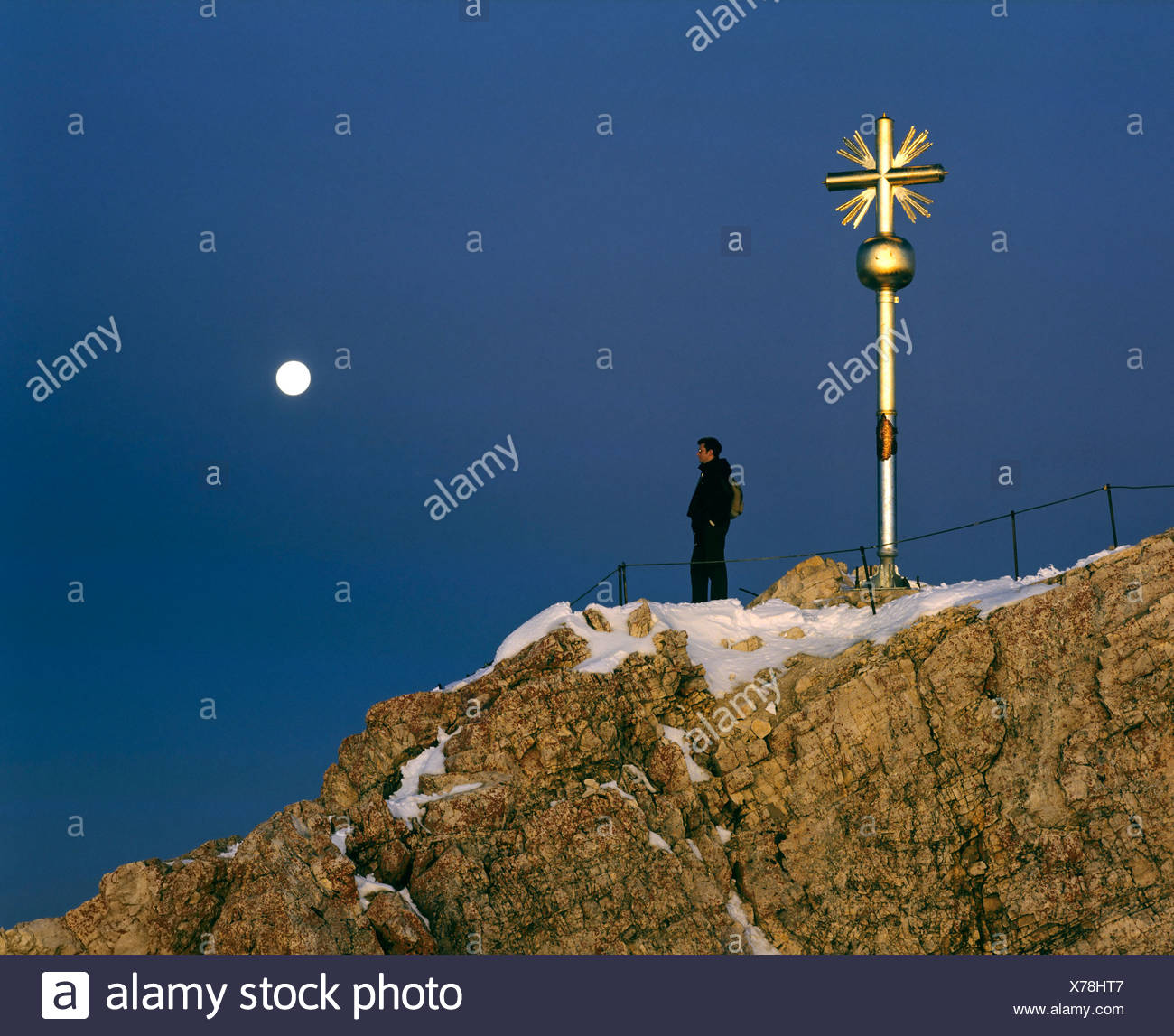 Summit cross at 2962 m or 9718 ft on the Zugspitze, Germany's highest mountain, at dusk, Wetterstein Range, Werdenfels Region,  - Stock Image