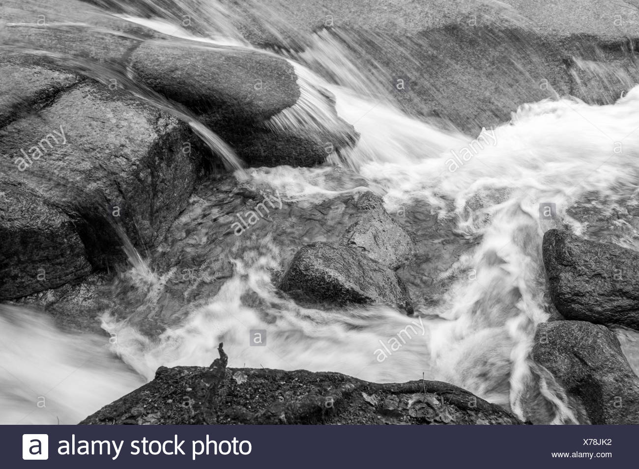 Water rushing and cascading over boulders in Flume Gorge. - Stock Image