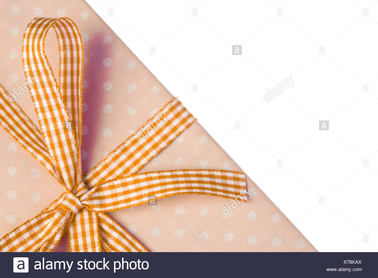Yellow gift wrapped present with gingham ribbon - Stock Image