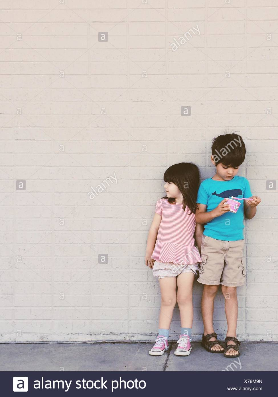 View Of Two Kids Standing Against The Wall - Stock Image