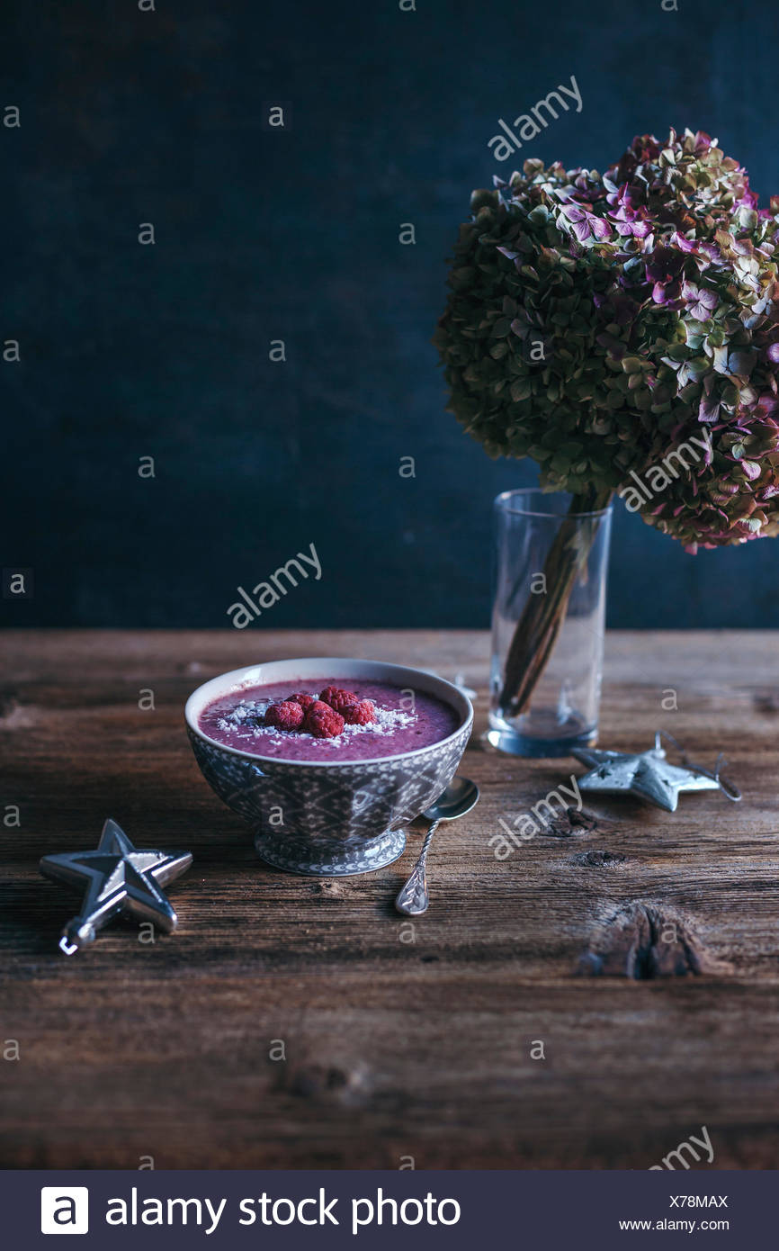 Raspberry smoothie in a bowl topped with shredded coconut and frozen raspberries - Stock Image