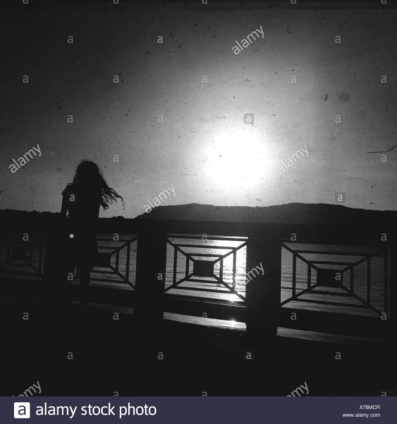 Silhouette Standing On Footbridge Over River Against Bright Sky - Stock Image