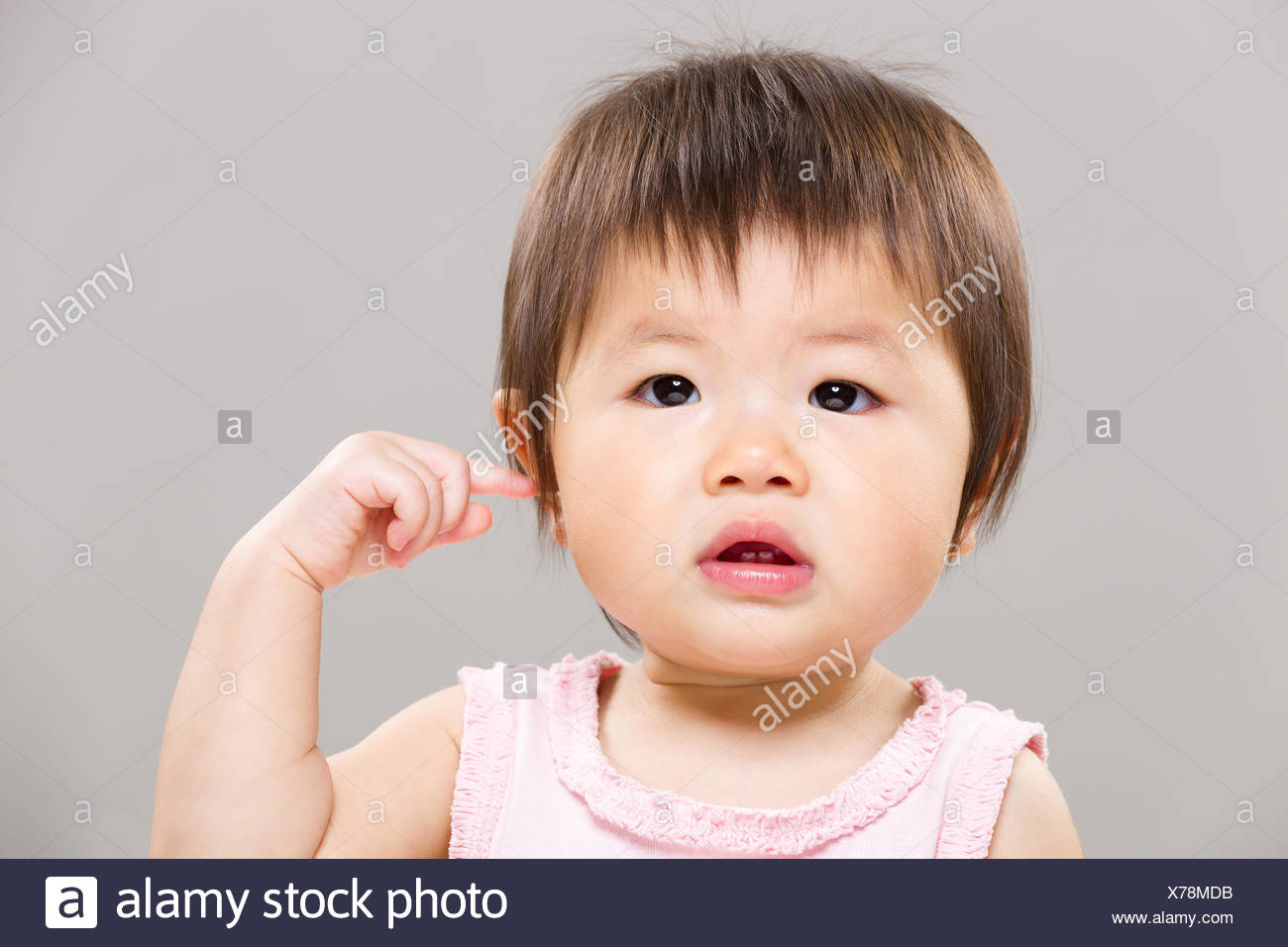 Baby girl touch her ear - Stock Image