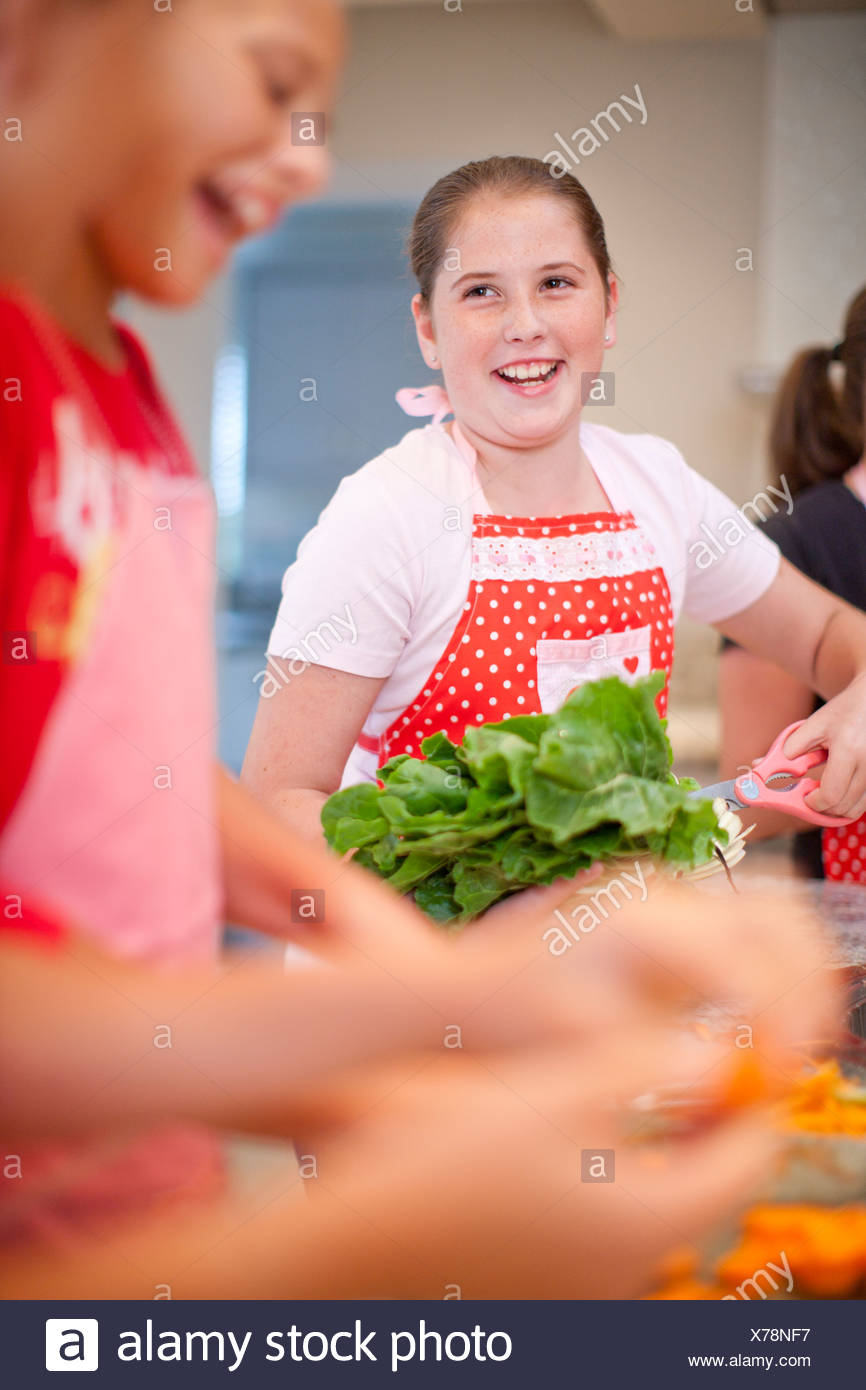 Teenage girls preparing vegetables in kitchen - Stock Image