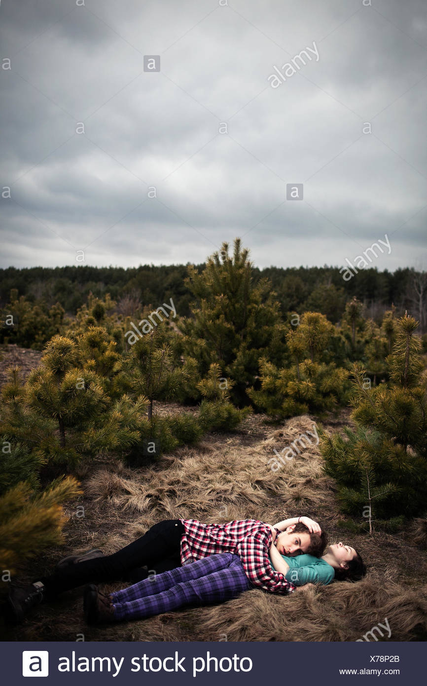 Teenagers (14-15) lying on ground and embracing - Stock Image