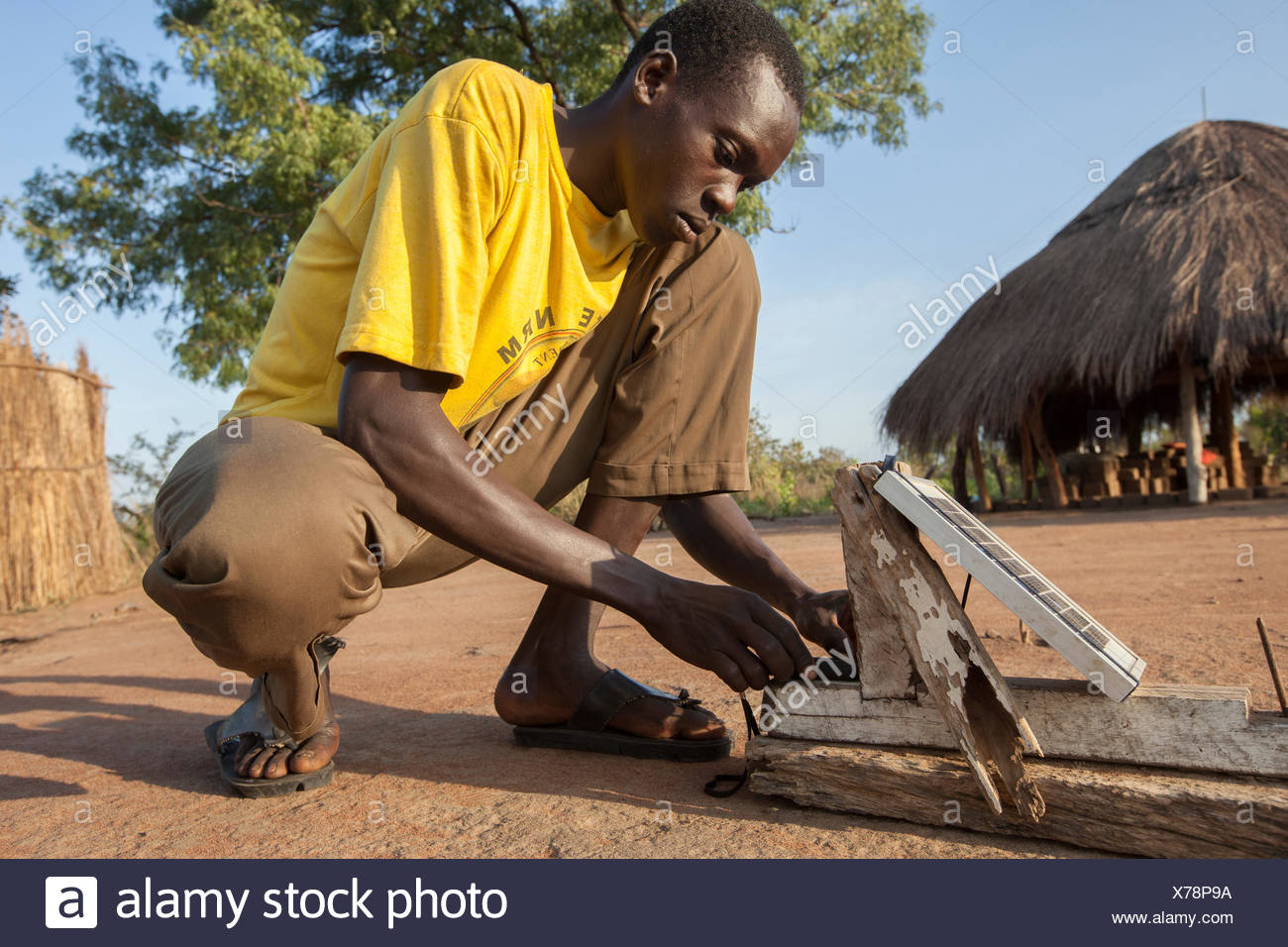 A young man uses a solar charger to power his mobile device. - Stock Image