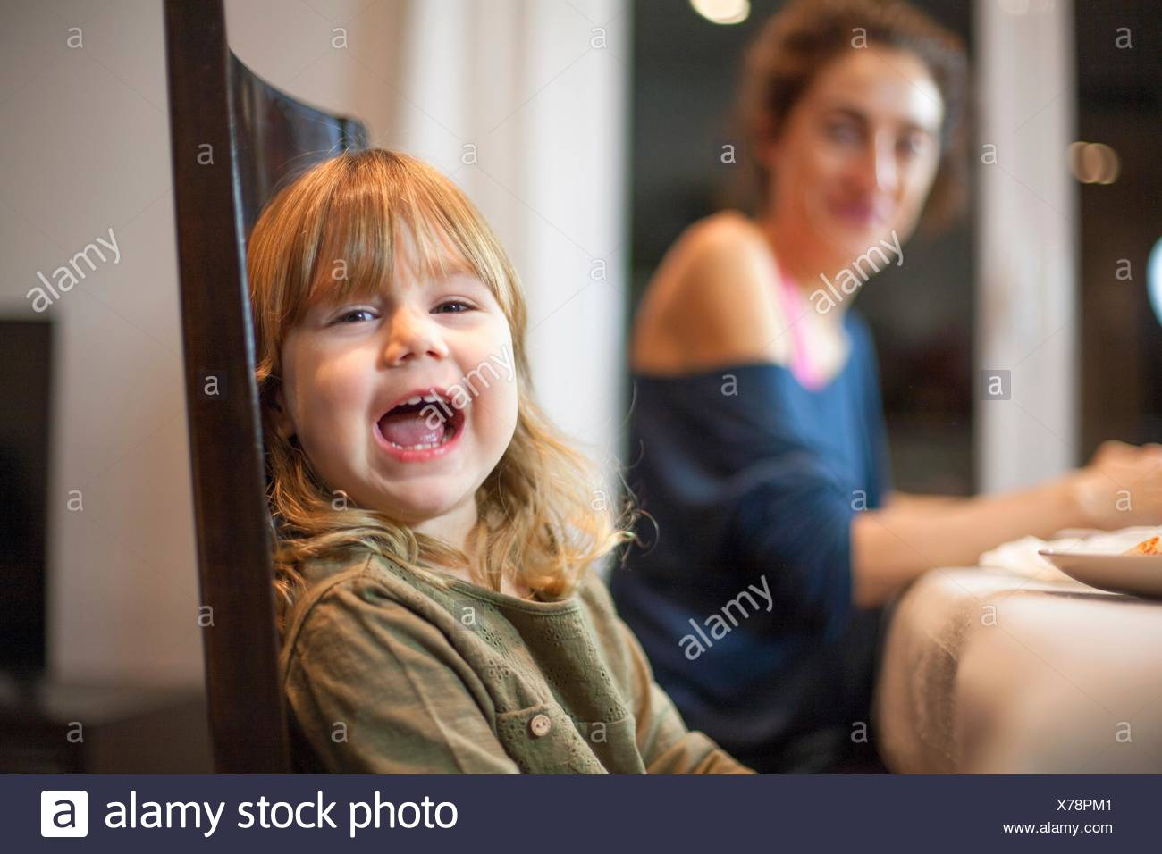 Three years old blonde child sitting at meal table with mother, looking at camera and speaking or shouting. - Stock Image