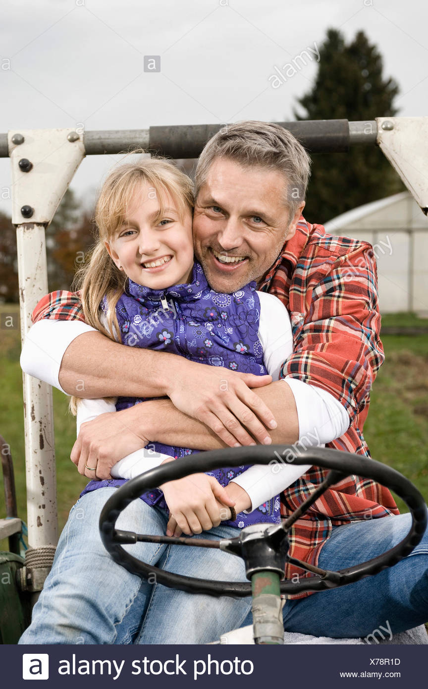 Farmer hugging daughter on tractor - Stock Image