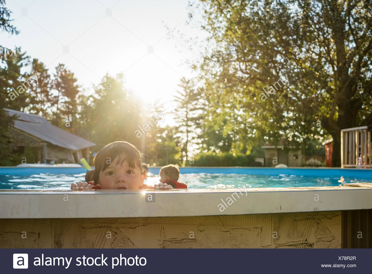 Boy peering over the edge of a swimming pool with siblings in the background - Stock Image