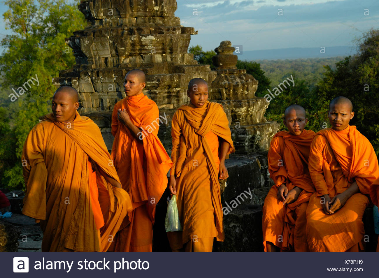 Five Buddhist monks in orange robes in Phnom Bakheng Temple, Angkor, Siem Reap, Cambodia, Southeast Asia Stock Photo