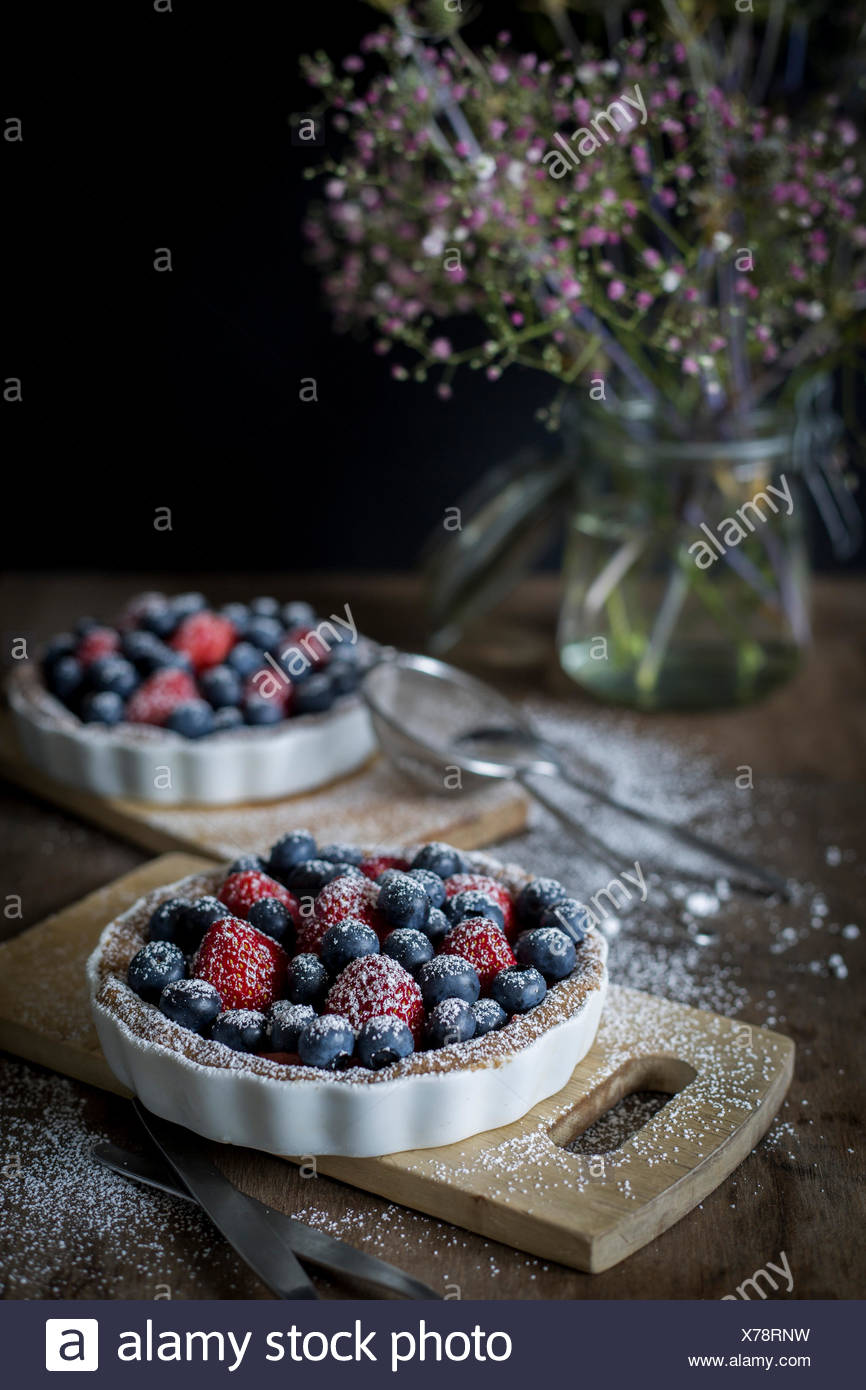 Berry tartetelets with icing sugar in baking dishes on wooden plates with bouquet of flowers in background - Stock Image