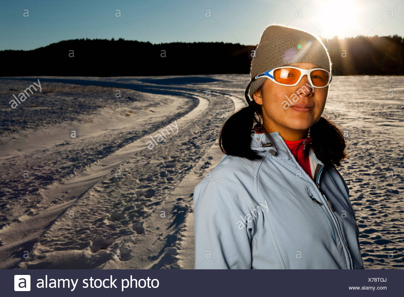 a Japanese-American woman has her portrait taken after running down a snowy road in Custer State, South Dakota. - Stock Image