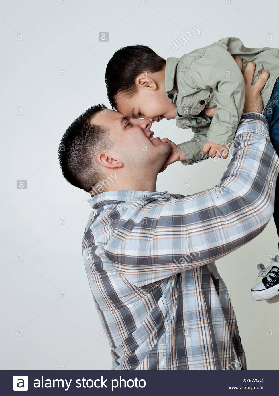 Young man holding son in the air, studio shot - Stock Image