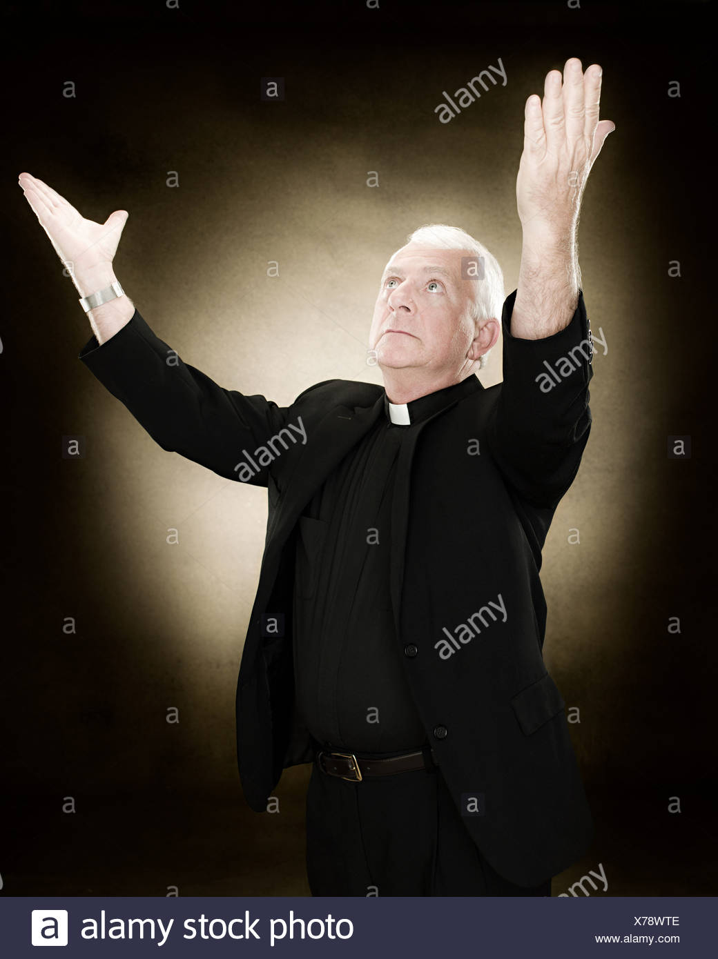 Priest with his arms raised - Stock Image