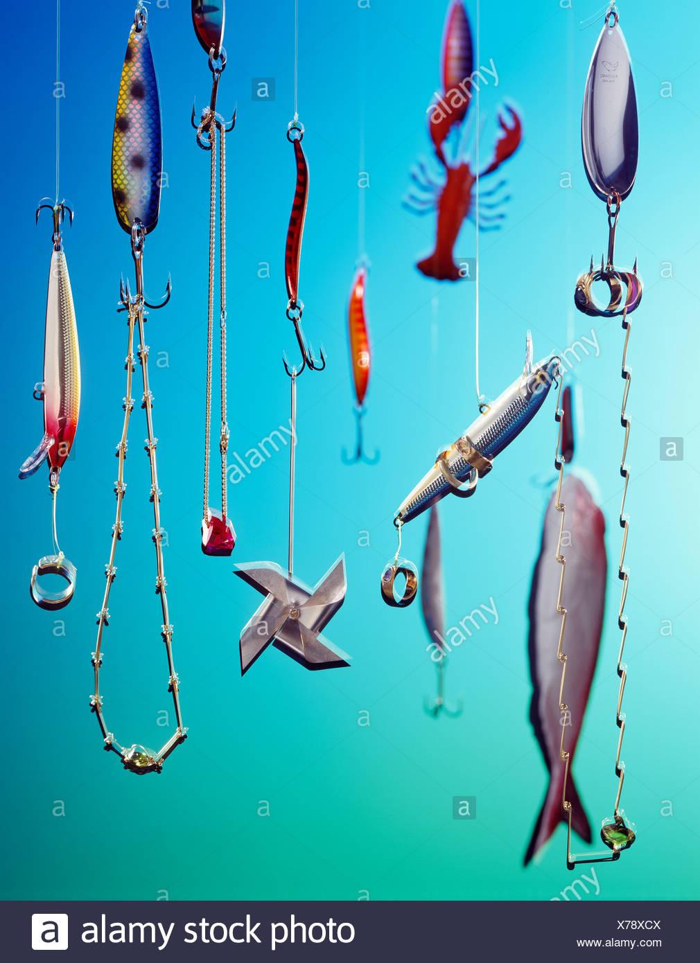 Jewelry on fish hooks, surreal - Stock Image