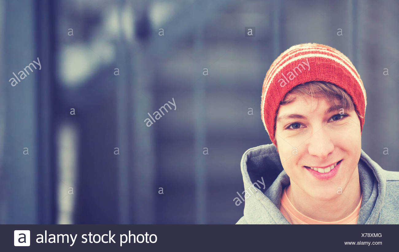 Smiling young man wearing a wool cap, portrait - Stock Image