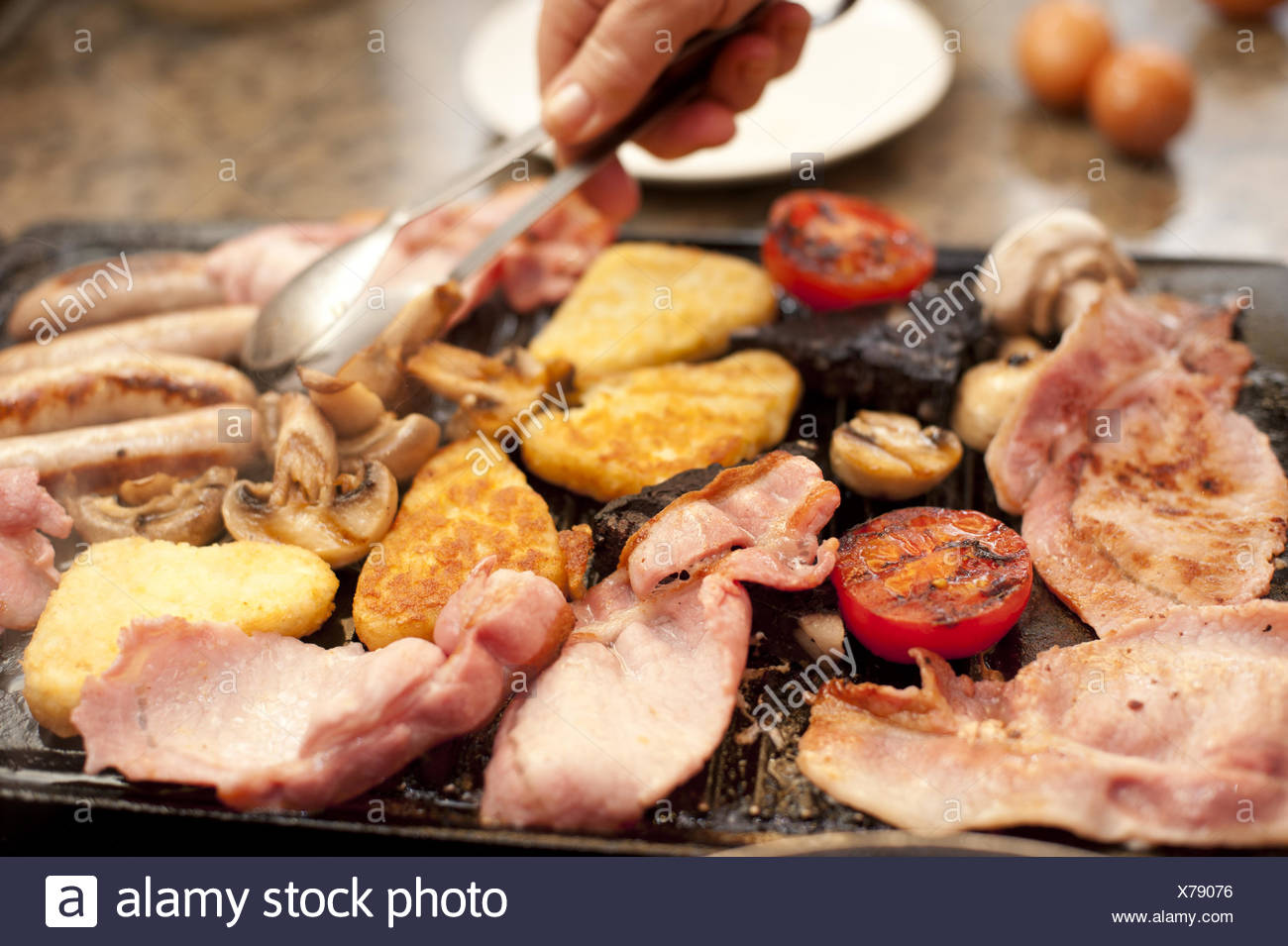 Man serving a hearty cooked breakfast - Stock Image