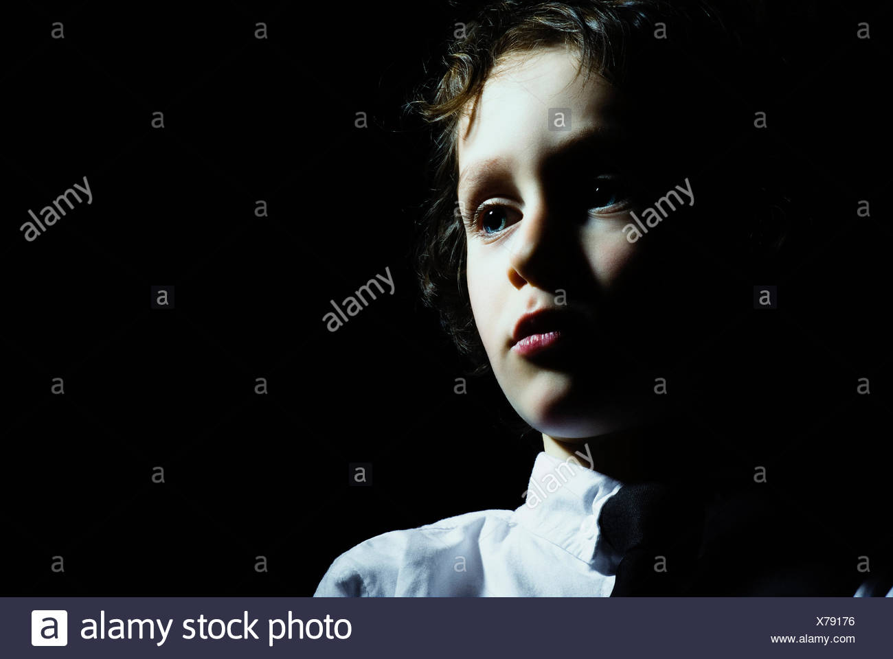 A young boy looking away in contemplation - Stock Image