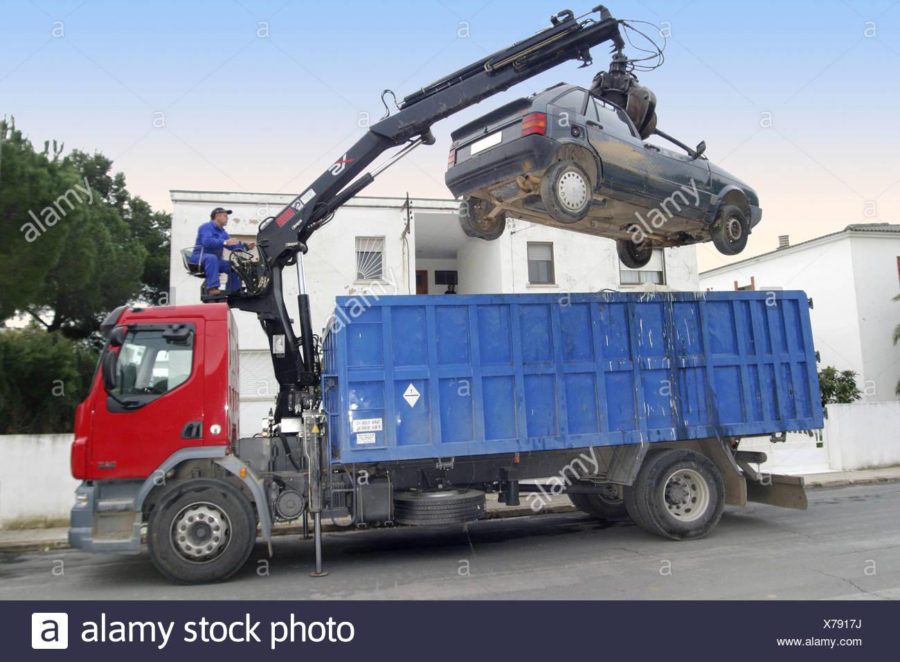 Truck with crane taking car to scrapyard - Stock Image