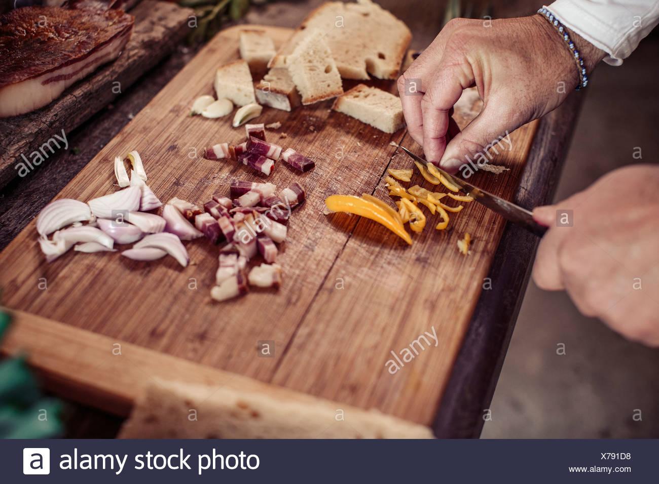 Person preparing dish, cutting ingredients - Stock Image