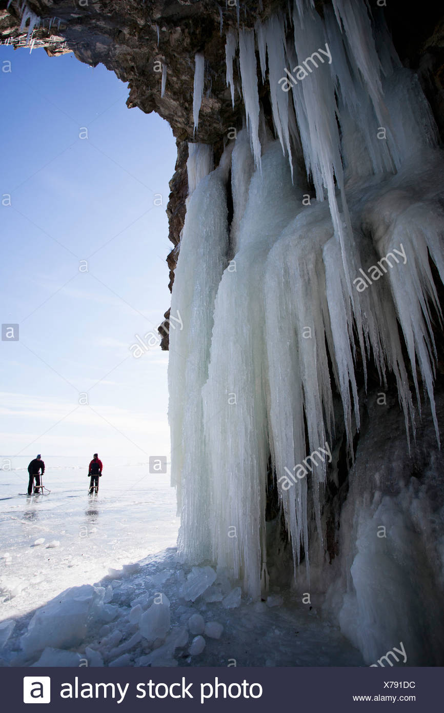 View of icicles with people hiking in background - Stock Image