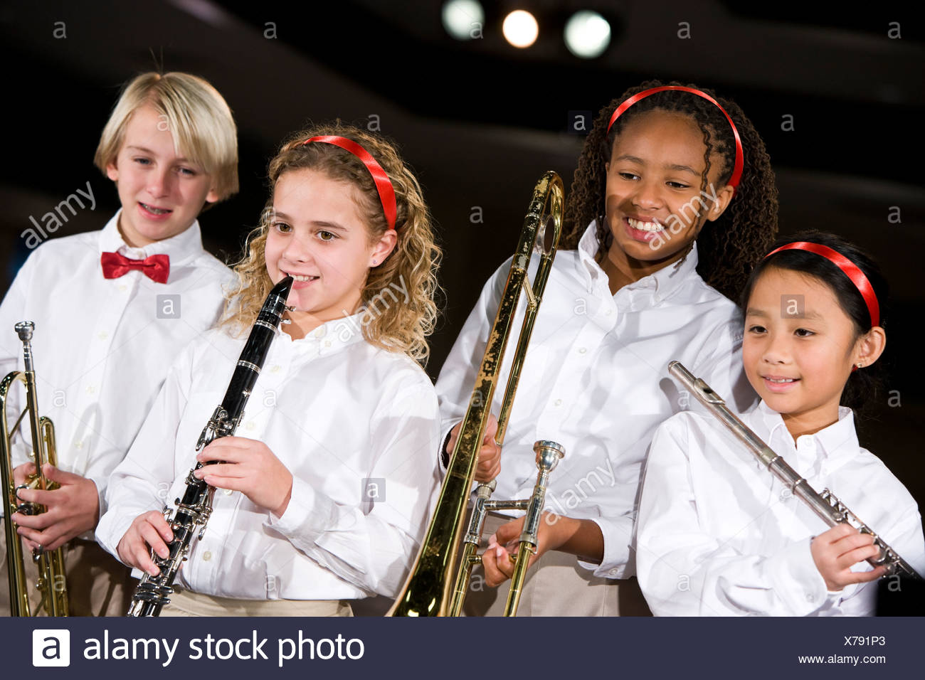 School children playing musical instruments in band - Stock Image
