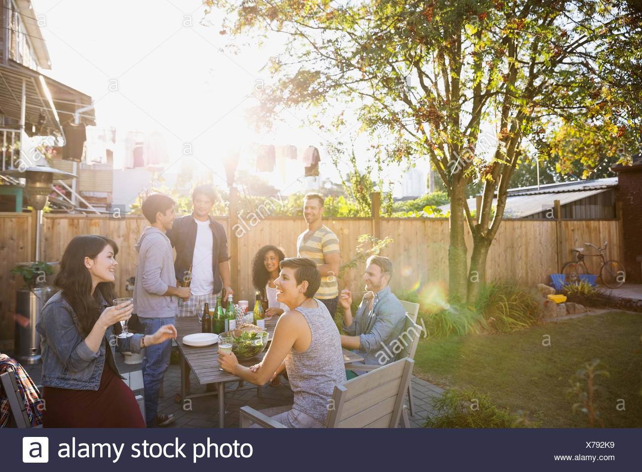 Friends eating and drinking at backyard barbecue - Stock Image