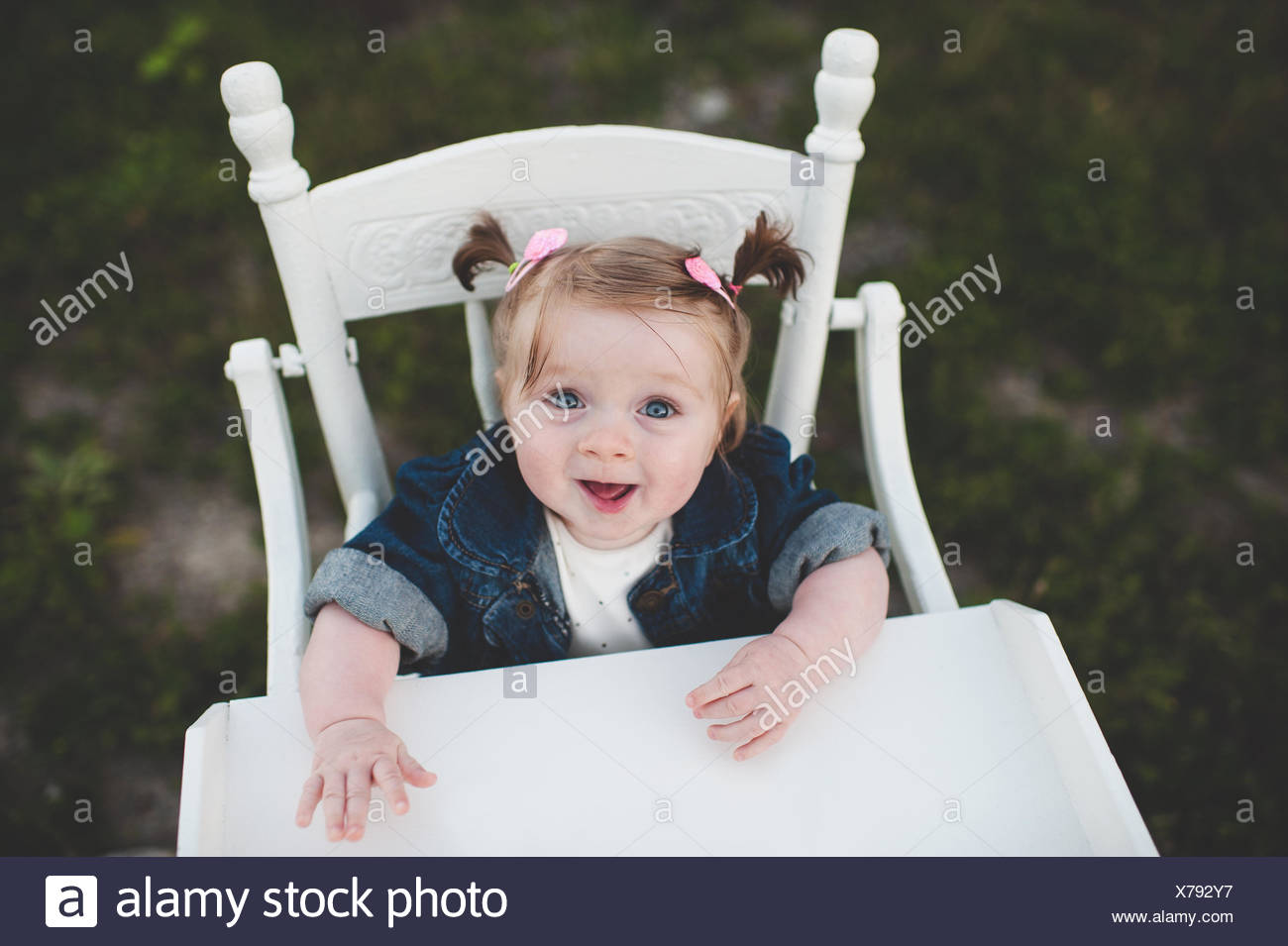 Portrait of baby girl in high chair Stock Photo