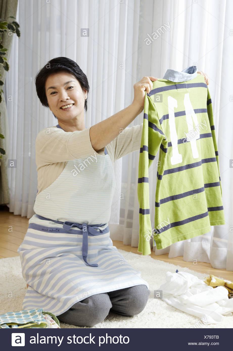 Woman folding laundry - Stock Image