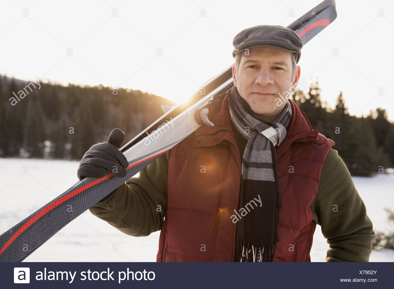 Portrait of man carrying cross-country skis - Stock Image