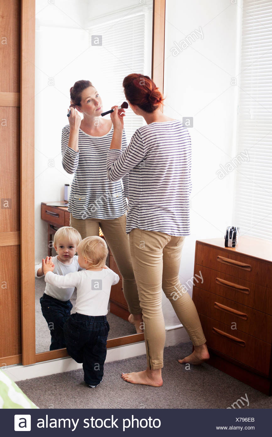 Woman applying make up with son at mirror - Stock Image