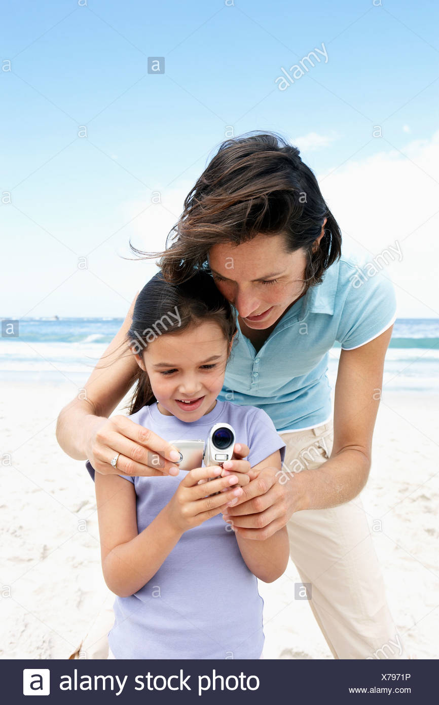 Mother and daughter 6 8 standing on beach using digital video camera - Stock Image