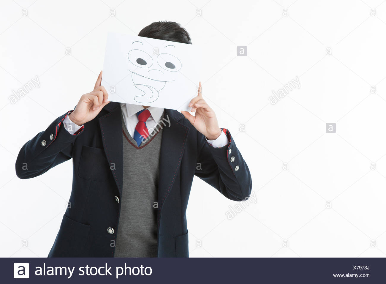 Portrait of school boy covering his face with a teasing mask - Stock Image